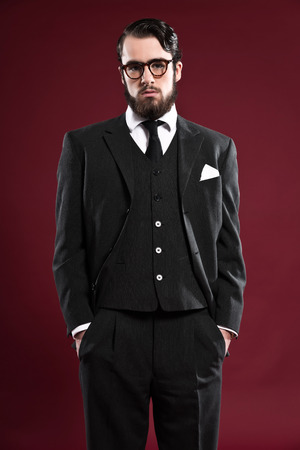 Retro 1900 fashion man with beard wearing grey suit black tie and glasses. Studio shot against red background. photo