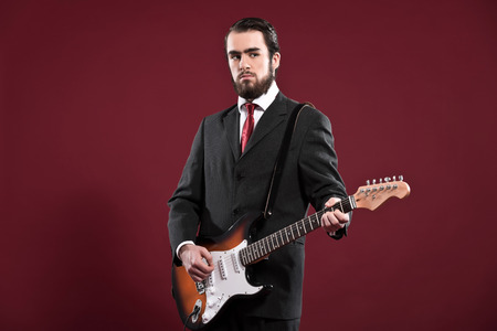 Retro fashion music man with beard wearing grey suit and red tie. Playing electric guitar. Studio shot. photo