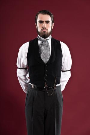 Retro 1900 Victoriaanse mode man met baard, gekleed in zwarte gilet en grijze stropdas. Studio opname tegen rode muur.