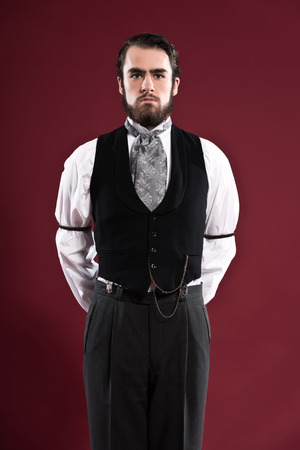 Retro 1900 victorian fashion man with beard wearing black gilet and grey tie. Studio shot against red wall.