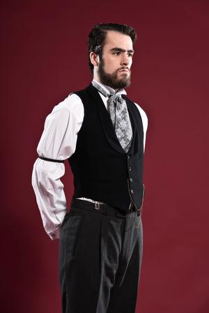 macho man: Retro 1900 victorian fashion man with beard wearing black gilet and grey tie. Studio shot against red wall.