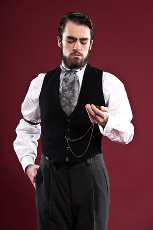 Retro 1900 victorian fashion man with beard wearing black gilet and grey tie. Holding pocket watch. Studio shot against red wall. Stock Photo