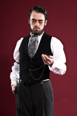 Retro 1900 victorian fashion man with beard wearing black gilet grey tie and glasses. Holding pocket watch. Studio shot against red wall. photo