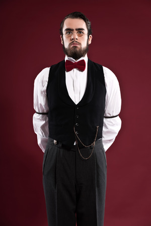 Retro 1900 victorian fashion man with beard wearing black gilet red bow tie and glasses. Studio shot. photo