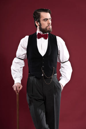Retro 1900 victorian fashion man with beard wearing black gilet and red bow tie. Holding a walking stick. Studio shot against red wall. photo