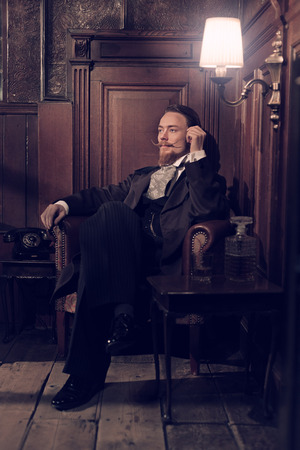Vintage 1900 fashion man with beard. Sitting in old wooden reading room. Smoking a cigar. Stock Photo