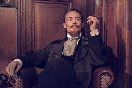 Vintage 1900 moda homem com barba. Sentado na antiga sala de leitura de madeira. Fumar um charuto.