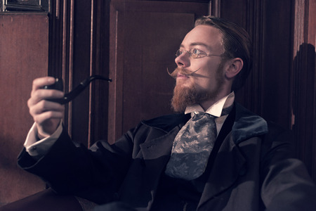 Vintage 1900 fashion man with beard and glasses. Sitting in old wooden reading room. Smoking pipe. photo