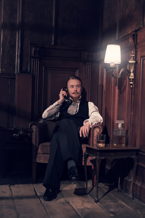 Vintage 1900 fashion man with beard. Sitting in old wooden reading room. Calling with telephone. photo