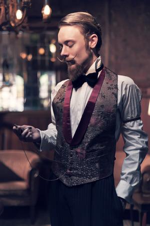 Vintage 1900 mode man met baard. Staande in de oude houten ruimte. Kijkend naar zakhorloge.