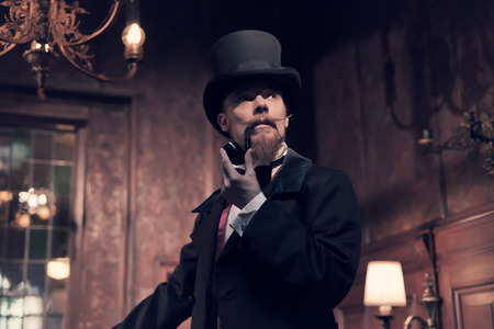 Vintage 1900 fashion man with beard. Smoking tobacco pipe. Standing in old wooden room. Wearing a black dickens hat.