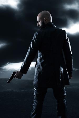 Gefährliche Gangster kahlen Mann mit Bart mit Pistole. Trägt schwarze Lederjacke. Dunklen bewölkten Himmel. Standard-Bild - 27404445