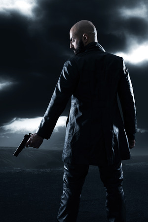 Dangerous bald gangster man with beard holding gun. Wearing black leather jacket. Dark cloudy sky.