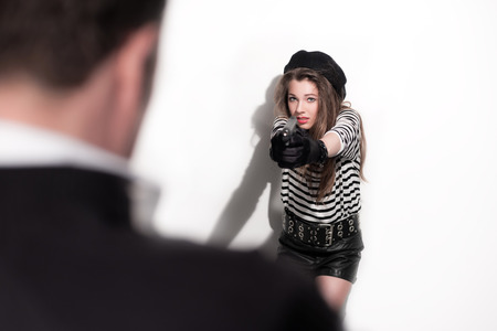 trespasser: Bold eighties fashion girl in black and white. Shooting on man. Studio shot against white wall.