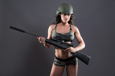 sexy army: Muscled fitness army girl holding gun. Wearing green helmet. Studio shot against grey.