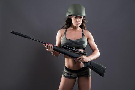 mujer con arma: Musculoso muchacha del ejército gimnasio sosteniendo la pistola. El uso de casco verde. Foto de estudio sobre gris. Foto de archivo
