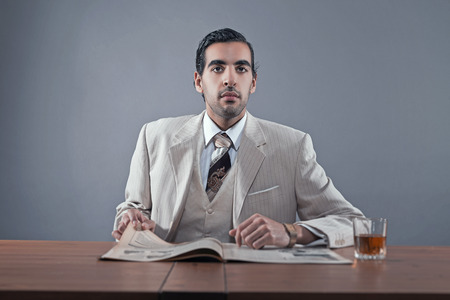 28295486 , マフィア ファッションの男が白のストライプのスーツ とネクタイを身に着けています。ウイスキーと新聞のガラスのテーブルに座っています。