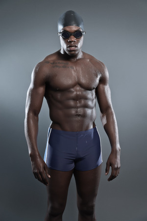 Athletic muscled black african swimmer wearing protective glasses and cap. Studio shot against grey. photo
