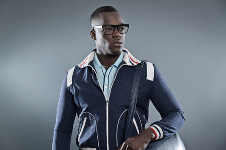 Retro college fashion black african man wearing blue jacket, leather bag and glasses. Studio shot against grey. photo