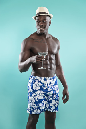 Summer black african american muscled fitness man holding cocktail drink. Wearing blue swimming shorts and hat. Studio shot against blue.