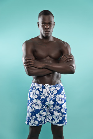 muscled: Black african american muscled fitness man. Summer swimwear fashion. Wearing blue swimming shorts. Studio shot against blue.