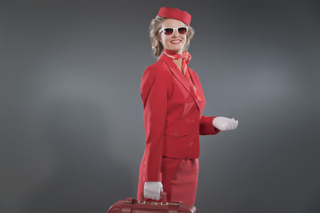 Retro blonde stewardess wearing red suit with cap and sunglasses. Holding red suitcase. Studio shot against grey. photo