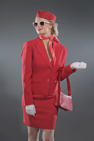 Retro blonde stewardess wearing red suit with cap and sunglasses. Holding red bag. Studio shot against grey. photo