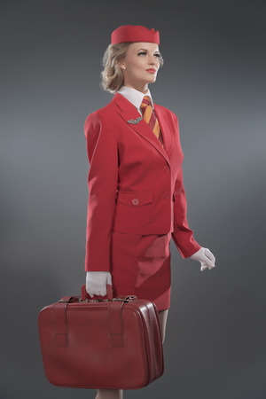 Smiling retro blonde stewardess wearing red suit with striped tie and cap. Holding red suitcase. Studio shot against grey. photo