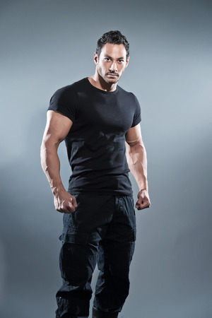 Combat muscled fitness man wearing black shirt and pants. Studio shot against grey. photo