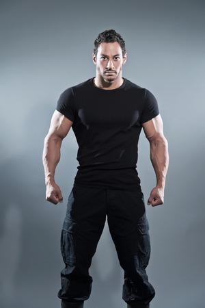 黒の t シャツとズボンを身に着けている筋肉フィットネス男と戦います。グレーに撮影スタジオ。