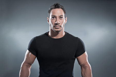 hombre fuerte: Combat Hombre musculoso gimnasio vistiendo camisa y pantalón negro. Foto de estudio sobre gris.