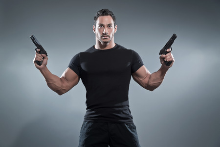 Action hero muscled man holding two guns. Wearing black t-shirt and pants. Studio shot against grey. photo