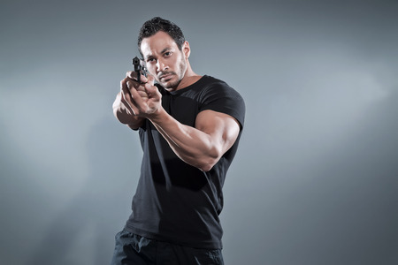 Action hero muscled man shooting with gun. Wearing black t-shirt and pants. Studio shot against grey.