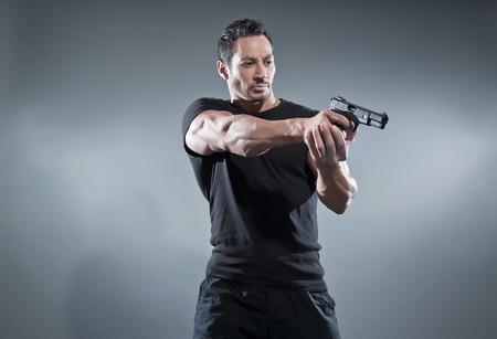 Action hero muscled man shooting with gun. Wearing black t-shirt and pants. Studio shot against grey.