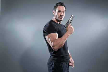 Action hero muscled man holding a gun. Wearing black t-shirt and pants. Studio shot against grey.