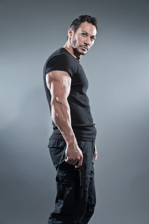 Action hero muscled man holding a gun. Wearing black t-shirt and pants. Studio shot against grey. Фото со стока - 28895437