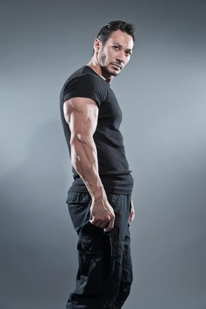 Action hero muscled man holding a gun. Wearing black t-shirt and pants. Studio shot against grey.