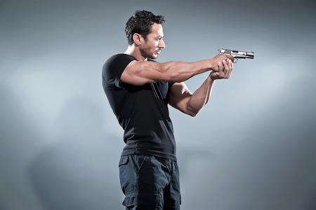 Actieheld gespierde man schieten met een pistool. Dragen zwart t-shirt en broek. Studio opname tegen grijs. Stockfoto
