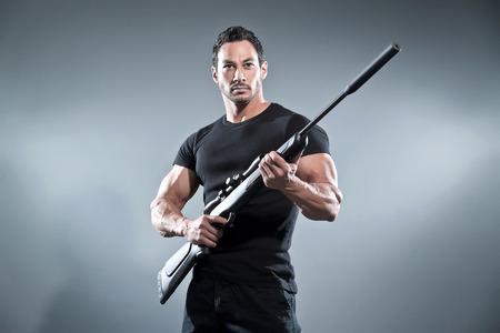 アクション ヒーロー筋肉男はライフルを保持しています。黒の t シャツとズボンを着ています。スタジオ撮影グレー。
