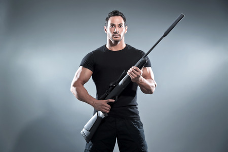 Action hero muscled man holding a rifle. Wearing black\ t-shirt and pants. Studio shot against grey.