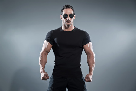 전투 바지와 선글라스와 검은 색 티셔츠를 입고 액션 영웅 남자를 가졌다. 스튜디오 회색에 대하여 총.