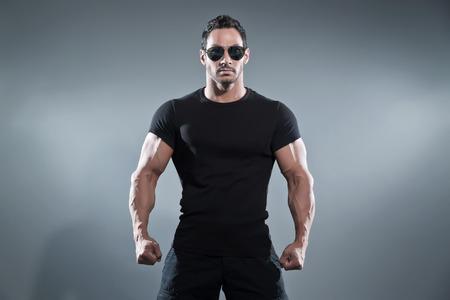 Combat musculoso héroe de acción hombre vestido negro camiseta con pantalones y gafas de sol. Foto de estudio sobre gris.