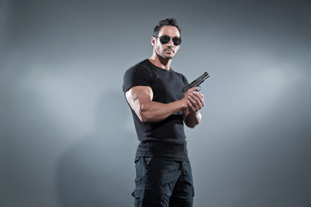 Action hero muscled man holding a gun. Wearing black t-shirt with pants and sunglasses. Studio shot against grey. Imagens - 28895447