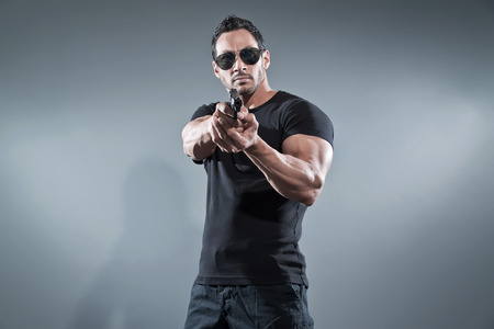 Action hero muscled man shooting with gun. Wearing black t-shirt with pants and sunglasses. Studio shot against grey.