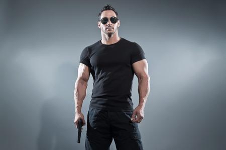 アクション ヒーロー筋肉男は銃を保持しています。黒の t シャツ パンツとサングラスを身に着けています。スタジオ撮影グレー。