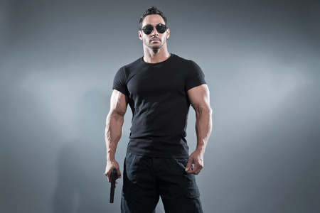 modelos hombres: H�roe de acci�n musculoso hombre con una pistola. El uso de negro camiseta con pantalones y gafas de sol. Foto de estudio sobre gris.
