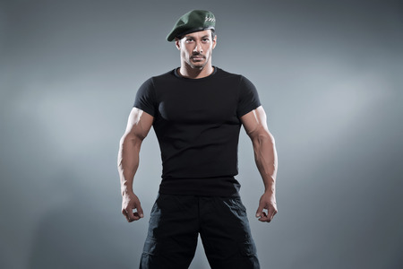 sexy army: Commander muscled action hero man wearing black t-shirt and pants. Studio shot against grey. Stock Photo
