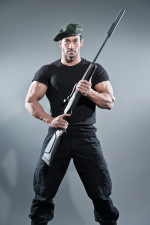 Commander muscled action hero man with rifle wearing black t-shirt and pants. Studio shot against grey.