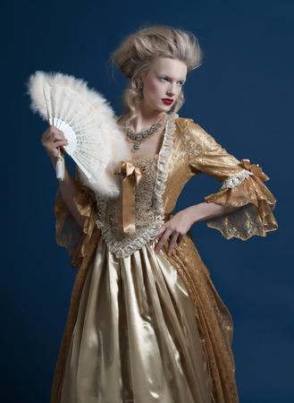 Retro baroque fashion woman wearing gold dress. Holding a fan. Studio shot against blue. Stockfoto