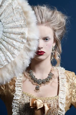 レトロなバロック様式のファッション女性ゴールドのドレスを着ています。ファンを保持しています。青に対して撃たスタジオ。